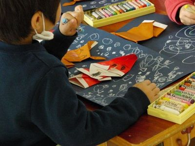 クリスマスを前に折り紙でサンタさんを作る男の子